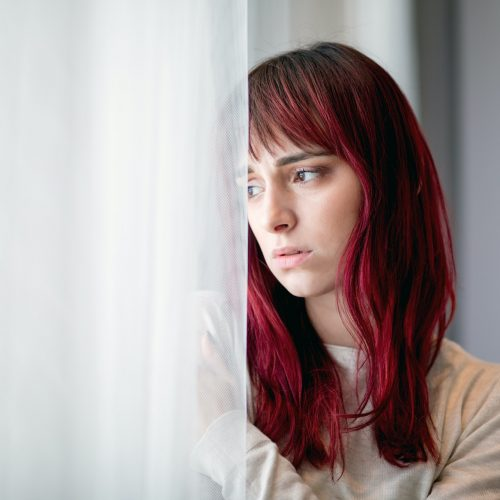 Depressed young woman near window at home thinking about unpleasant experiences